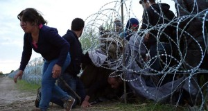 Syrian refugees cross into Hungary underneath the border fence on the Hungarian - Serbian border near Roszke, Hungary on Aug. 26, 2015. The number of refugees entering Hungary has reached a new high as the government hurries to build a 4-meter (13-foot) fence on the Serbian border to stop them. More than 140,000 migrants have reached Hungary on routes across the Balkans so far in 2015. Recently, some 80 percent of them are from war zones like Syria, Iraq and Afghanistan. (ANSA/AP Photo/Bela Szandelszky)